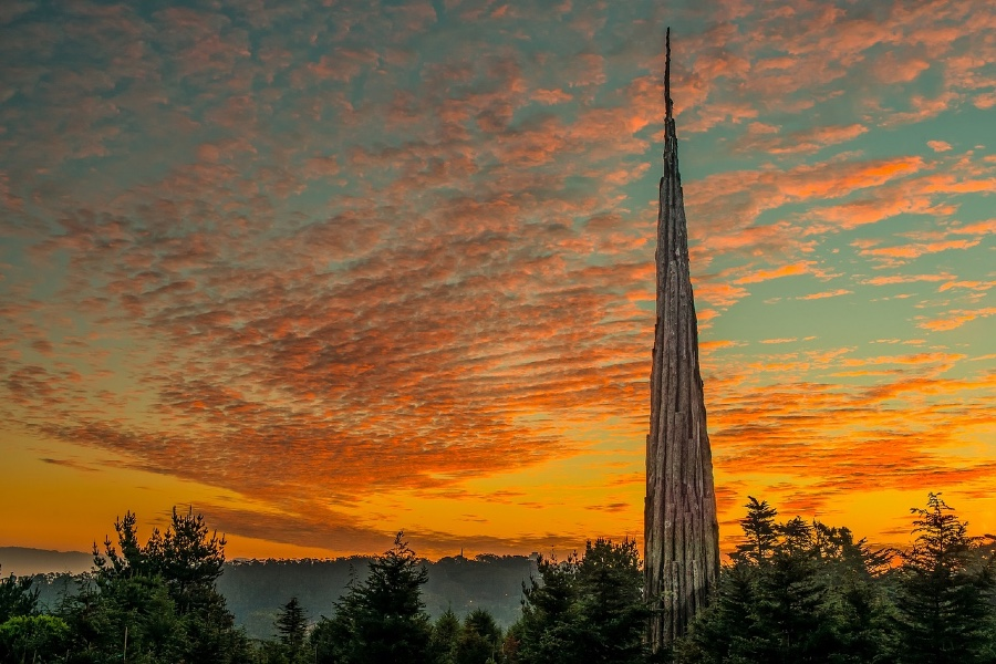 Andy Goldsworthy's Spire statue peeks through the horizon at sunset in Presidio National Park