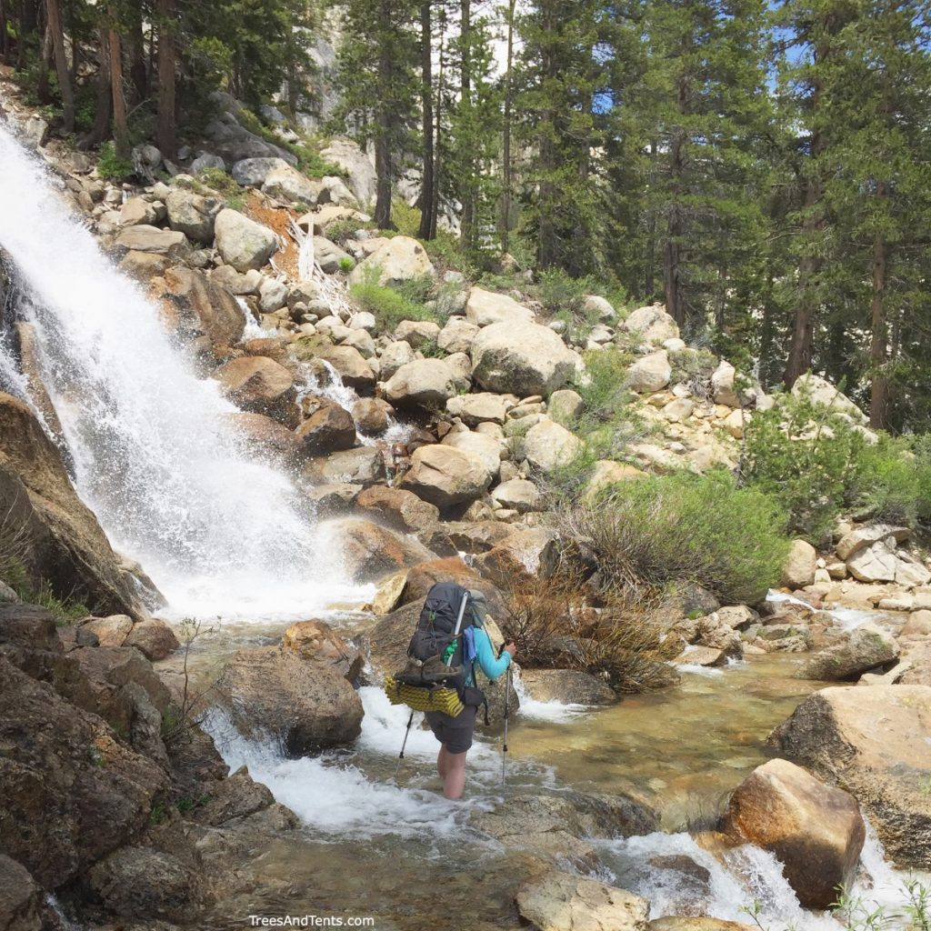 The options are limitless when you are backpacking. Picture of a woman crossing a waterfall while backpacking the John Muir Trail.
