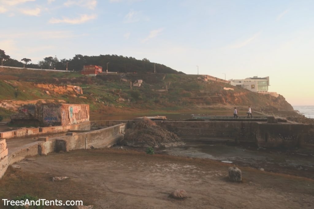 Two people walk the walls of the Sutro Baths ruins.